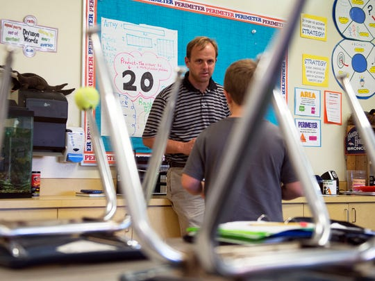Fourth-grade teacher Geoff Kinsey works with a student
