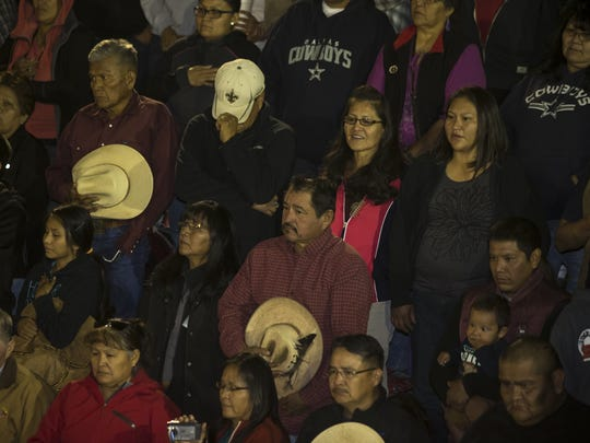 Spectators in Ken's Arena stand for a traditional cowboy's prayer and the national anthem, both delivered in Navajo, before the start of the  Kenny Young Bull Riding Classic in Page.