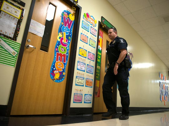 Henderson County Sheriff deputy Steve Geyer checks classrooms during a training lockdown of the Marlow Elementary School Thursday morning.