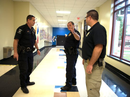 Henderson County Sheriff deputies Steve Geyer, Jesse Blankenship and Neil McDonald talk about security doors  during a training lockdown of the Marlow Elementary School Thursday morning.