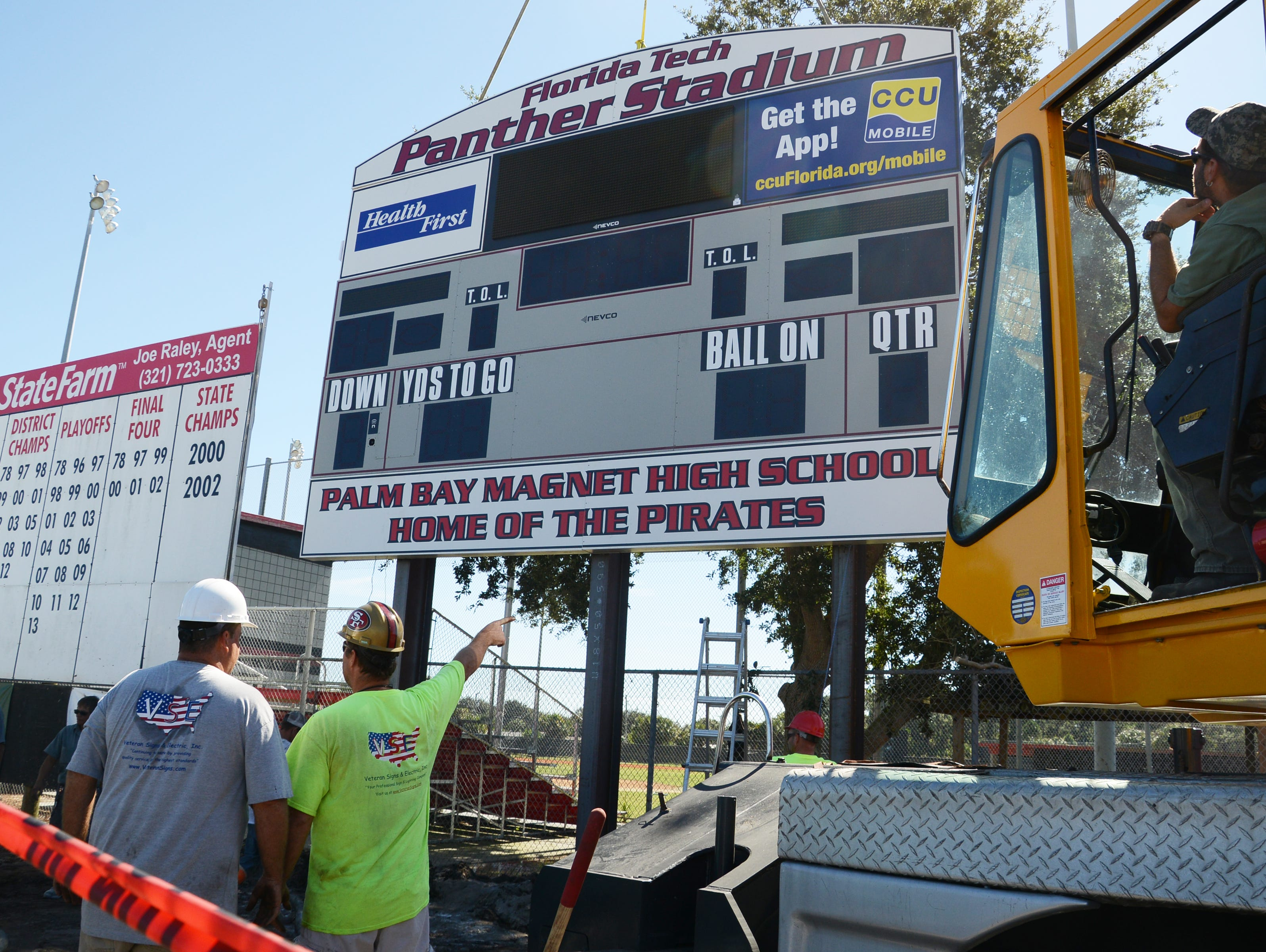 Workers install the new scoreboard sign at Panther Stadium in Melbourne Friday.