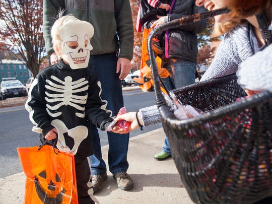 Tallis Reichert, 3, trick-or-treats outside Pufferbellies in downtown Staunton on Saturday, Oct. 31, 2015.