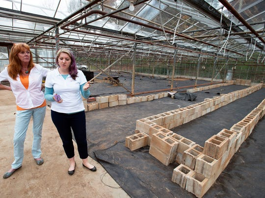 August Forbes and Sally Eason stand on the floor of their new Sunburst grow facility in West Asheville where fresh, locally grown is expected to be delivered to local restaurants by next month. At right, a long, large tank will be used to grow fish.