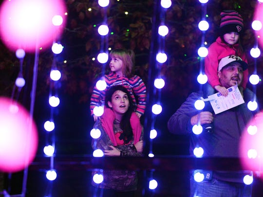 """Sitting atop Jayda Kindley's, 14, shoulders, Payton Miller, 3, left, checks out the """"Lights of the Season"""" twinkling tree with Piper Miller, 4, riding on Joey Kindley's shoulders as they visit the Winter Lights at the North Carolina Arboretum during a media preview on Thursday, Nov. 19, 2015. The lights are on display until Jan. 2."""
