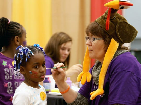 Emoni Burns, of North Avondale has a her face painted by Jana Smith of Crossroads Church during Give Back Cincinnati's Fall Feast at Duke Energy Convention Center in 2015. This is the 14th year where those in need could get a free Thanksgiving Day meal, along with health screening, coats, hair cuts and more