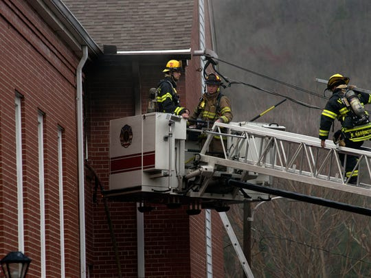 Asheville Fire Department firefighters work to contain and extinguish a fire from an upper level of the MorningSide Baptist Church in East Asheville Wednesday afternoon.