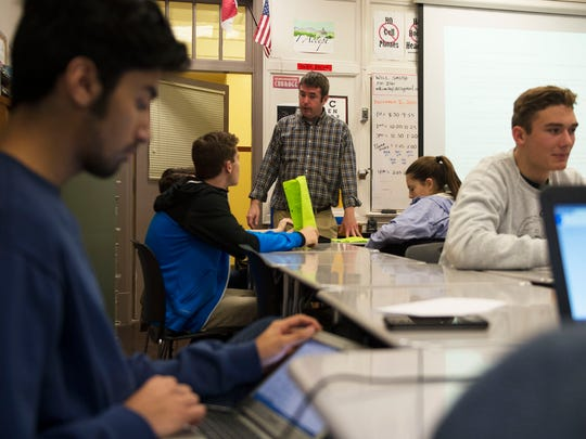 Asheville High School teacher Will Smith, center, discusses upcoming class work with students in his class Tuesday.