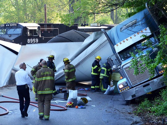 Members of the Asheville Fire Department remove diesel fuel from a tractor-trailer that had collided with a train at a Glendale Avenue crossing in 2016. Firefighters are increasingly being diagnosed with cancer due to contaminants encountered in the line of duty.