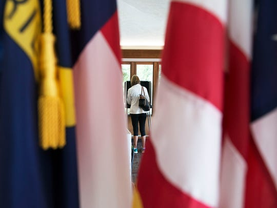 A woman is seen casting a ballot in between both a North Carolina State and the United States flags at the Buncombe County Board of Elections building located at 77 McDowell St. on Dec. 9, 2015.