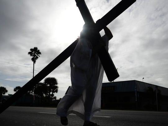 Brian Bucci carries the cross in Saturday's The Bible on Parade event in Melbourne Dec 5.