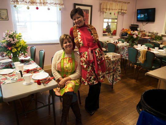 Volunteers Simone Wood and Dianne Petit prepare the dining room at the Steadfast House during Christmas Day festivities Friday.