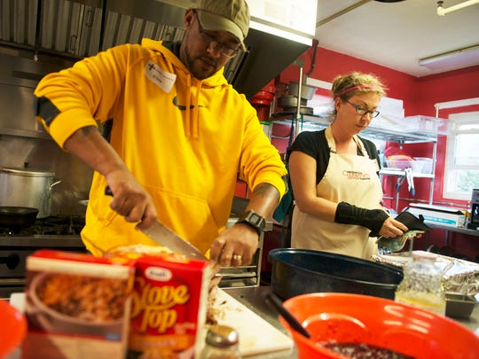 Volunteers Elvis and Rebecca Lafunor prepare food at the Steadfast House during Christmas Day festivities Friday.