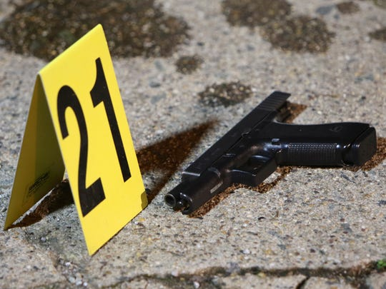 A gun sits by a marker following a shooting Friday,