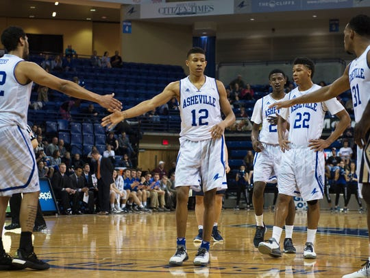 UNCA's Raekwon Miller, 12, is congratulated by teammates after shooting a free throw in the first half of a game against Charleston Southern Wednesday at Kimmel Arena.