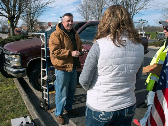 John McClung, left, talks about items with his wife, Carrie, and Tim Bayless, right, in a parking lot off Haywood road Saturday morning.