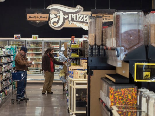 Shoppers browse various food items for sale in the