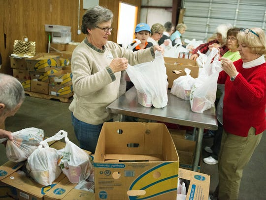 Volunteers with the MANNA Food Bank pack food into bags during a MANNA Packs for Kids program packing session in this file photograph.  The program provides food slipped into needy students' backpacks on Fridays when school is in session and Mission Hospital listed support for it as one of the community benefits it provided in its 2015 tax return.