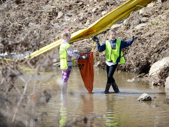 Sally Quarrier, 10, left, and Sofi Zuber, 9, clean up trash in a stream leading to the French Broad River near Asheville Waste Paper on Lyman Street as their Carolina Day School fourth-grade class volunteers with Asheville GreenWorks on Wednesday, Feb. 17, 2016. Other students with the school removed invasive species of plants as their volunteer work.