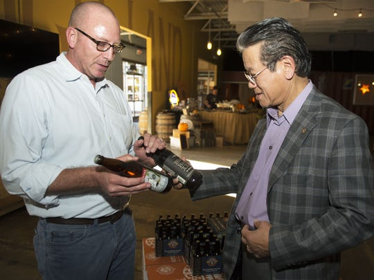 Deschutes Brewery President Michael LaLonde greets Highland Brewing Company founder Oscar Wong with a bottle of Deschutes' famous Black Butte Porter and an bottle of IPA.