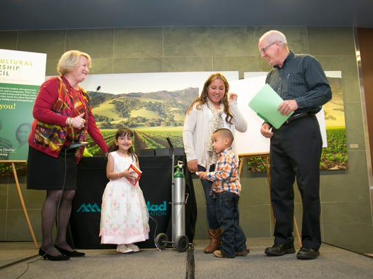 Linda Ford, President of Natividad Medical Foundation accompanied by two children and their mother who are graduates of Natividad Medical Center's Neonatal Intensive Care Unit, presenting a thank you to John D'Arrigo.