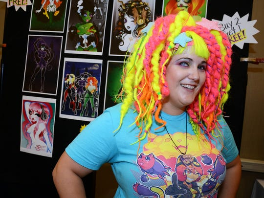 Illustrator Katie Hazzard stands at her booth during