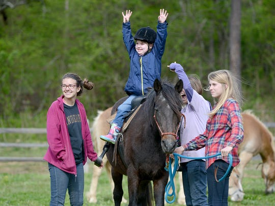 """Olivia Landreth, 8, goes """"no hands"""" atop Biscuit as Hayden Bailey, 14, left, Auburn Bailey, 12, and their aunt Robin Hughes help walk them around the pen at Sweetwater Youth Ranch on Thursday, April 7, 2016.  The ranch is considered a ministry rather than therapy and relies on the horses natural therapeutic abilities to help children."""