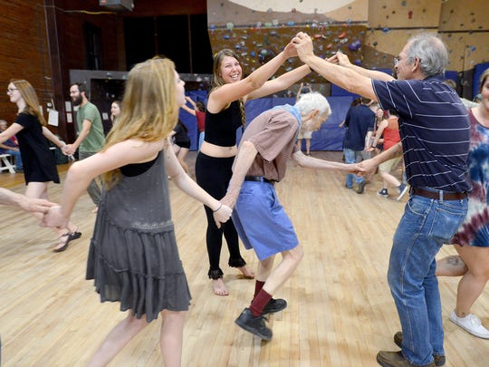 Hannah Dineley, center, makes a bridge with her partner as other dancers make their way under their arms during the Old Farmer's Ball at Bryson Gym on the campus of Warren Wilson College on Thursday, April 21, 2016.