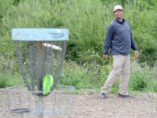 "Ryan Pickens, author of ""The Definitive Guide to Disc Golf,"" smiles as he watches his white disc go into the basket while throwing a few warm-up putts before the start of a tournament at Richmond Hill Park on Tuesday, May 17, 2016."