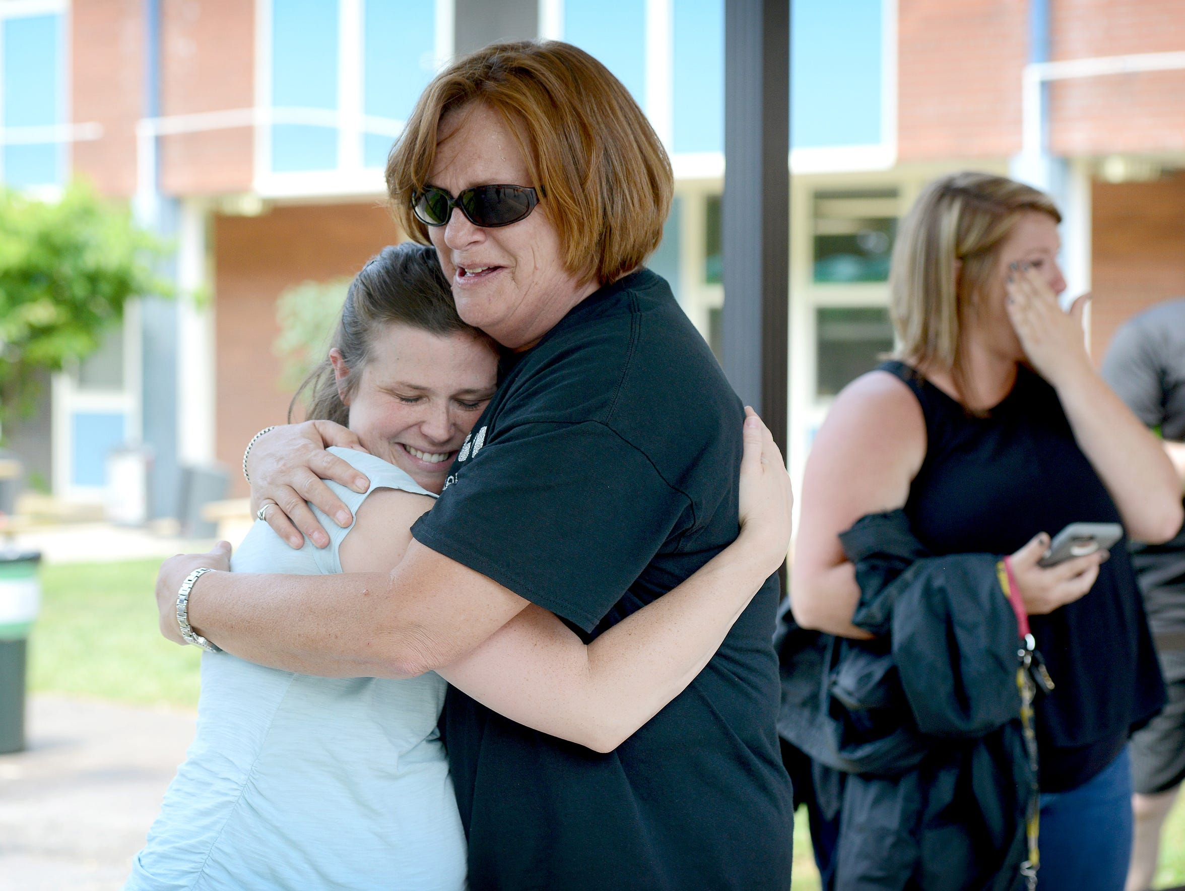 Fourth grade teacher Darsey Fox hugs her teaching assistant