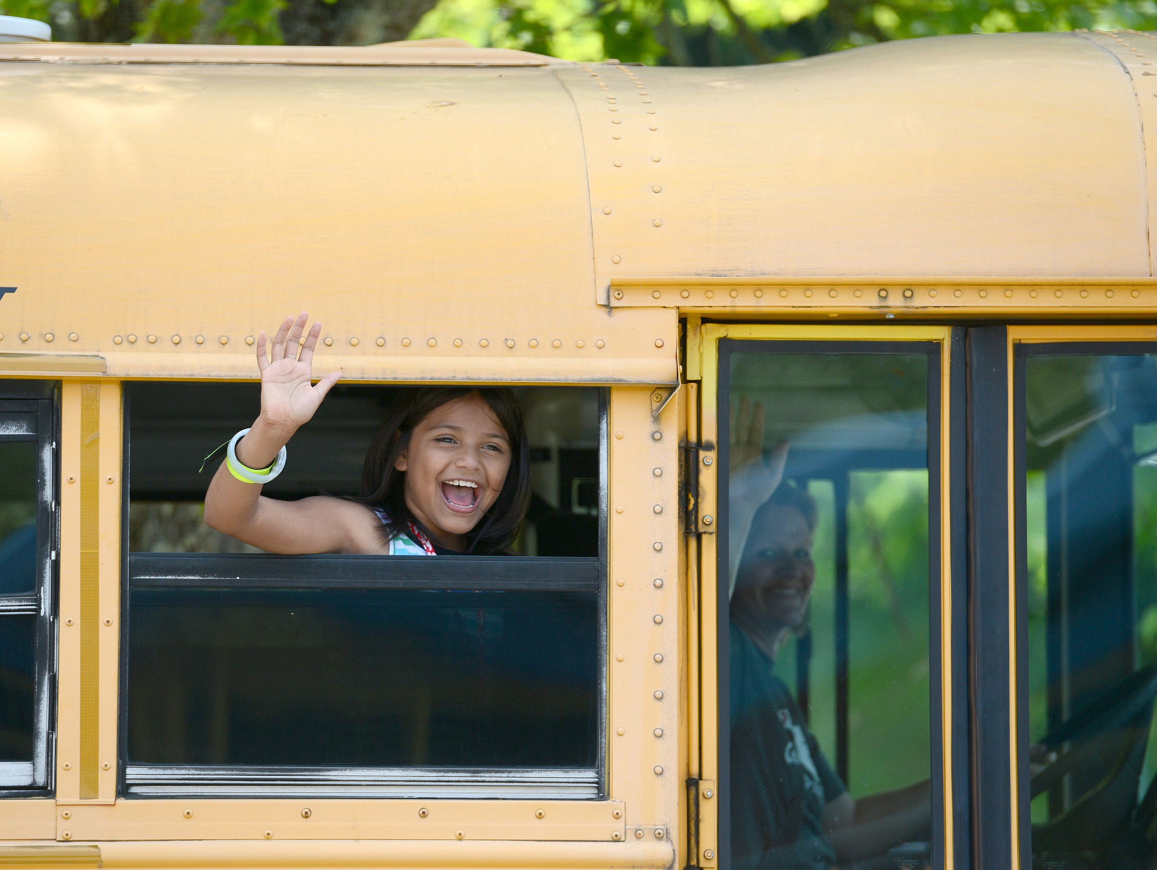 Angelina Gayosso-Hensley waves to teachers as her bus