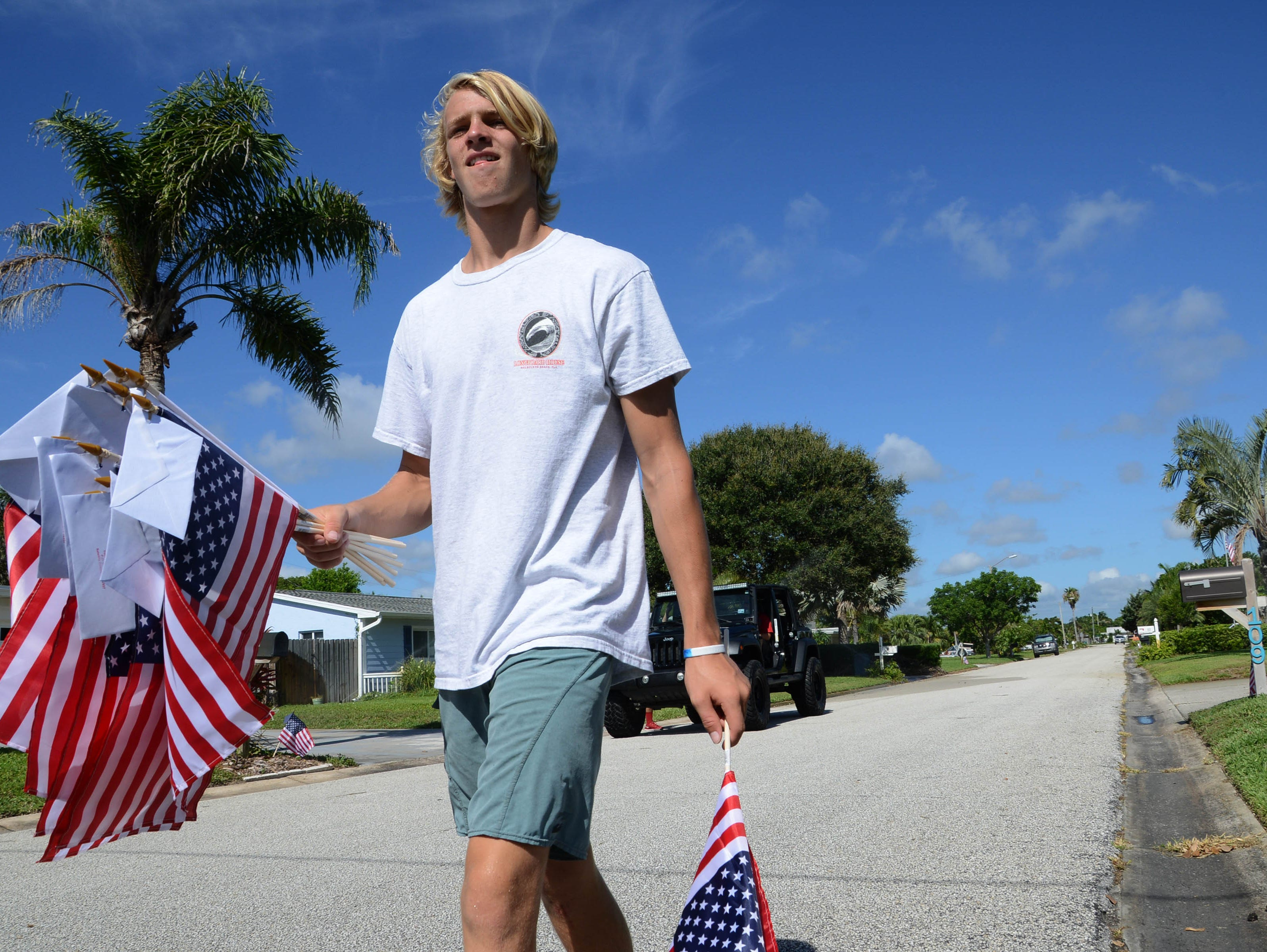 Noah Mumme helps set out American flags Thursday morning in Satellite Beach. Students from Satellite High's football and ROTC squads help distribute American flags as part of a fundraiser for the school.