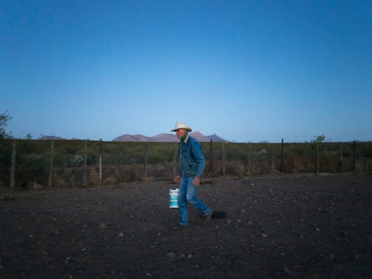 A rancher walks across the open land in Douglas, Arizona.
