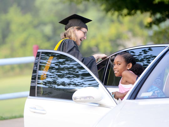 Carrie Allen, Asheville City Schools Elementary Director, helps Nevaeh Kenney, 9, out of her car for the start of the first day at Hall Fletcher Elementary School on Wednesday, July 20, 2016.