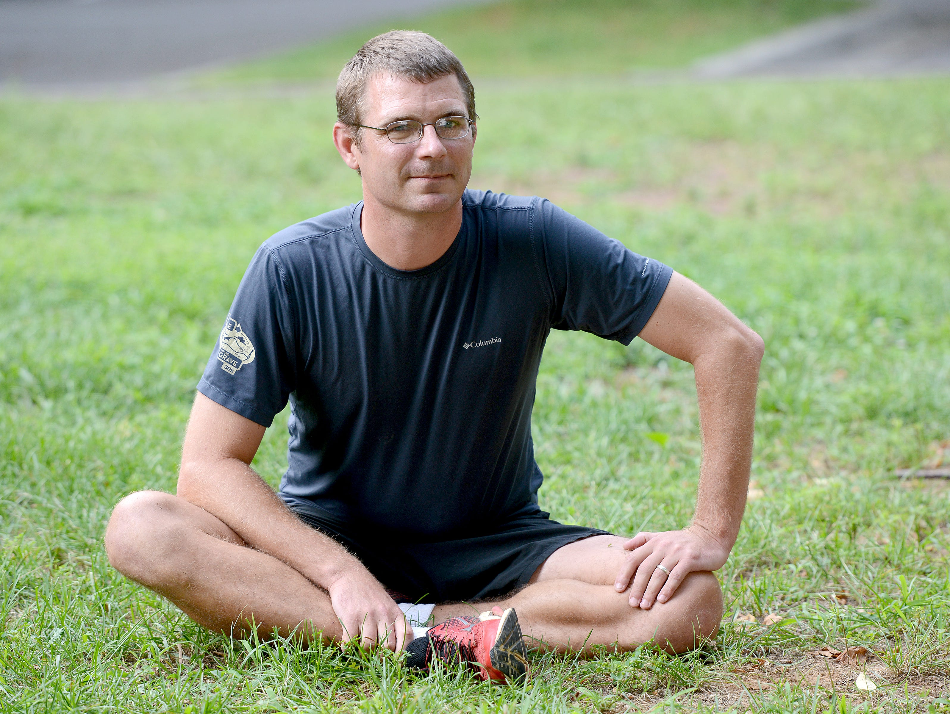 Roberson's new cross country coach Tom Ferguson stretches with the team before a workout at the North Carolina Arboretum on Thursday, Aug. 4, 2016. Ferguson took over for David Culp who stepped down from the role in December.