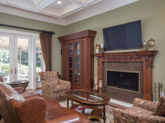 The family room has a gas fireplace, coffered ceiling and atrium doors to the patio area.