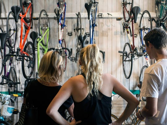UofL student Megan Fell, along with her mother Jeanine and Parkside Bikes salesman Brent Wesley, weighs her options for a bike. The purchase is partially financed with a $400 voucher from a campus program Fell completed. 8/22/16