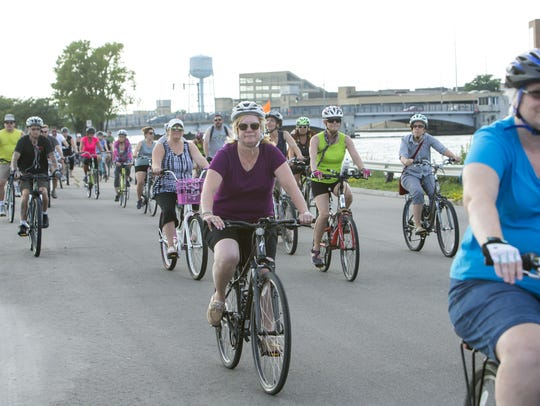 Bicyclists ride as a group on the Slow Roll ride through