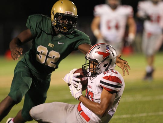 City High's Naeem Smith pulls in a catch past West