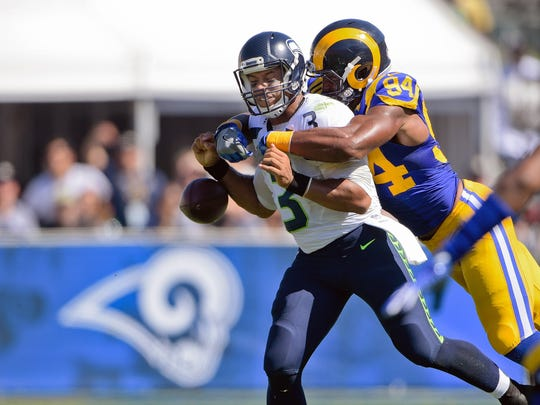 Seahawks quarterback Russell Wilson (3) looses the ball as he is sacked by Rams defensive end Robert Quinn during Sunday's game at the Coliseum.