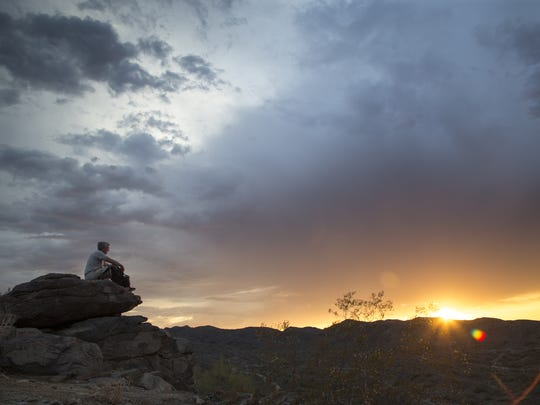 Don Eydenberg of Phoenix watches the sunset at South Mountain Park's Pima Canyon.