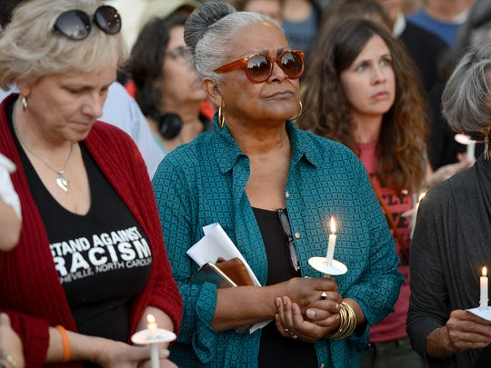 Carmen Ramos-Kennedy, center, holds a candle in vigil