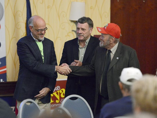 Commissioners Joe Belcher, left, and Mike Fryar shake hands with then-candidate Robert Pressley during a November 2016 Buncombe County Republican party event. The political makeup of the county board could change if courts allow recently drawn maps to be used for the 2020 election.