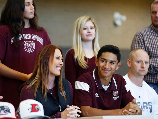 Robbie Merced smiles before signing a national letter