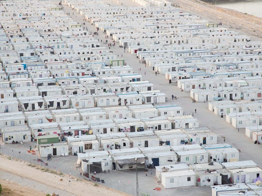 "This undated photo provided by MoMA shows a photograph of Nizip II, a Container Camp in Turkey on the Syrian border. The photograph is part of the exhibit ""Insecurities: Tracing Displacement and Shelter,"" at the museum in New York. The new exhibit invites visitors to take an entirely new look at the concept of home and design, this time through the lens of migration and global refugee emergencies, in which temporary shelters, organizers say, are being deployed on a scale akin to that after World War I."