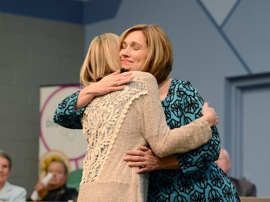 Amy Churchill hugs her daughter, Maddy, after being