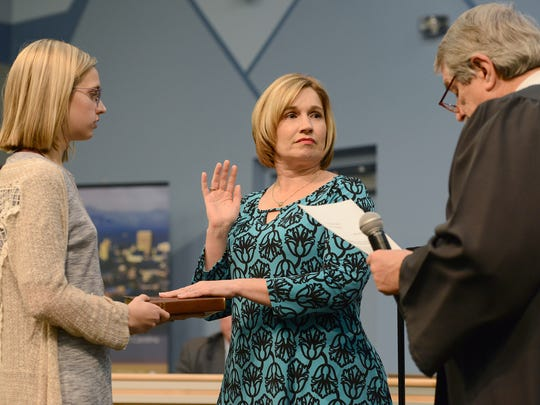 Amy Churchill is sworn in to the Buncombe County School Board by Judge Marvin Pope as her daughter, Maddy, holds the bible for her at the Buncombe County Schools central office on Thursday, Dec. 1, 2016.