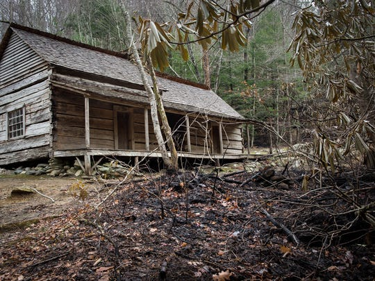 "The historic Noah ""Bud"" Ogle cabin sits unharmed just feet from burned brush in the Great Smoky Mountains National Park near Gatlinburg, Tenn., Wednesday, Dec. 7, 2016."