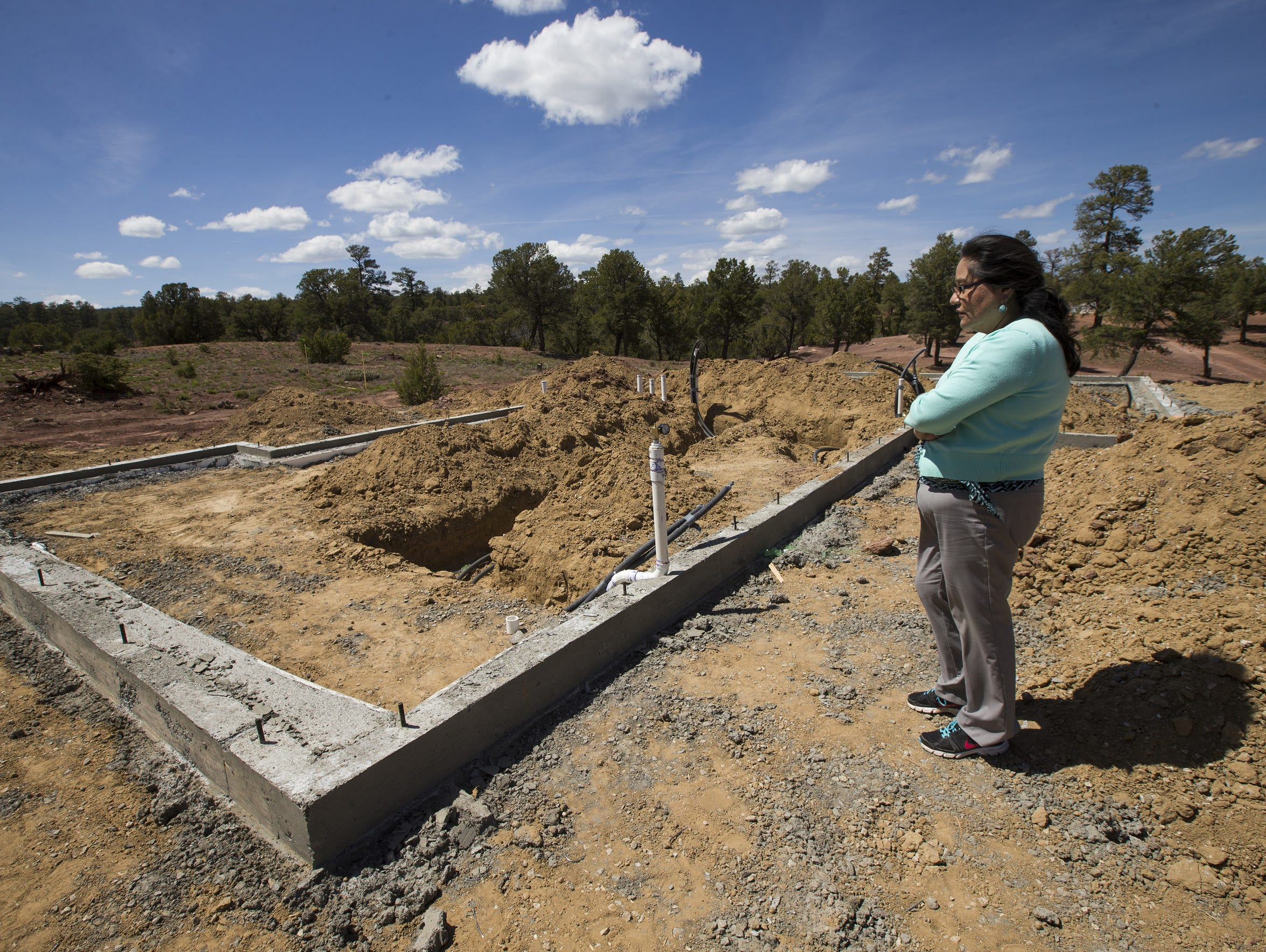 Pauletta Tsosie looks over the foundation of her new