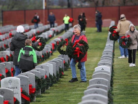 People participate in Wreaths Across America on Saturday
