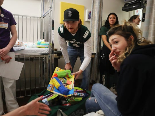 Shasta College quarterback Tim Naylor gives toys to Jessica Brewster and her 1-month-old daughter, Sky Lee Humphreys, as her sister Jennifer Burns, right, looks on Wednesday. Student-athletes from Shasta College gave toys to children at Mercy Medical Center in Redding from a toy drive held at the college in November.